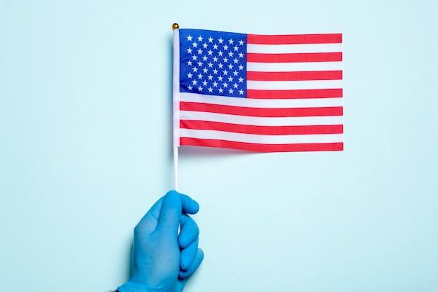 미국 의학 및 건강 관리 개념 의료용 장갑에 손을 얹은 손은 의료 종사자 고품질 사진의 밝은 파란색 배경의 날에 미국 국기를 들고 있습니다.
