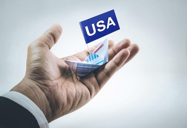 ビジネスマンの手で紙グラフで作られたボートと旗の米国メッセージ