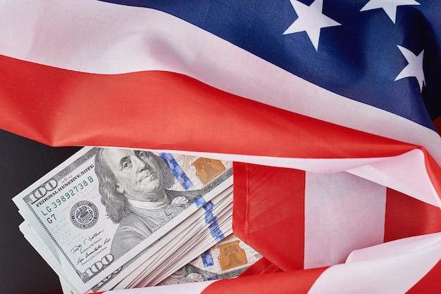 暗闇の中でアメリカ国旗とドル紙幣。ファイナンスの概念