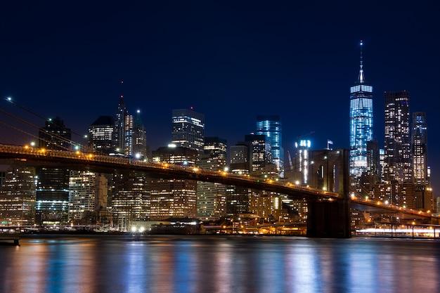 Сша. нью-йорк. вечер. вид на огни небоскребов манхэттена, ист-ривер и бруклинский мост