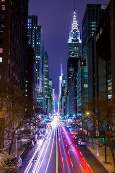 Сша, нью-йорк. манхэттен. ночь 42 ул. высокие здания, уличные фонари и автомобильные фары