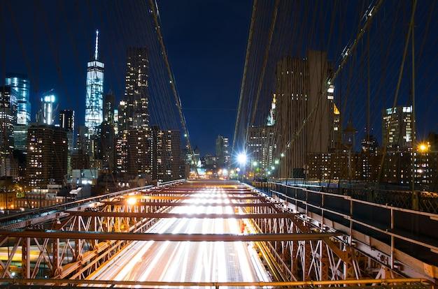 미국. 뉴욕시. 밤의 브루클린 다리. 다리의 교통량과 맨해튼의 고층 빌딩의 전망