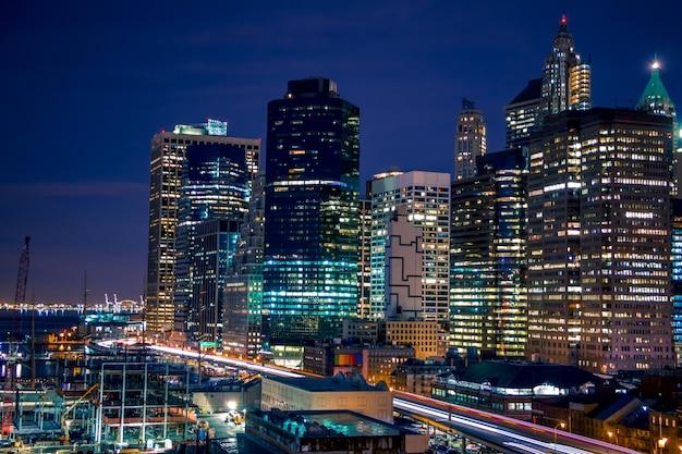 미국, 뉴욕시. 맨해튼의 밤 부두. 고층 빌딩, 야간 조명 및 건설