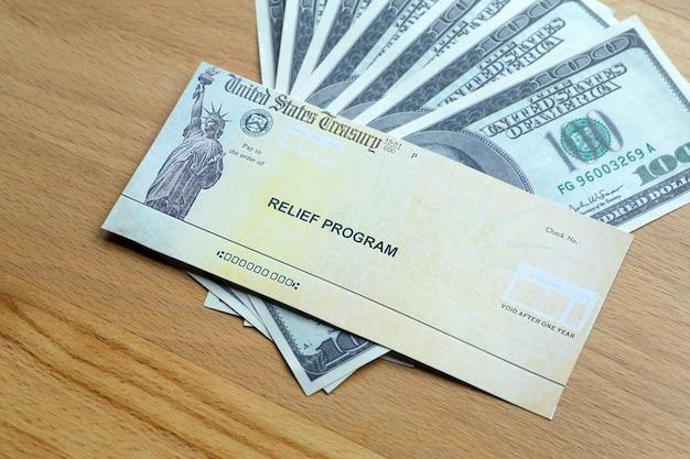木製の背景にドル紙幣を米国救済プログラム小切手