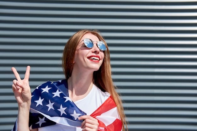 Usa stars and stripes flag. joyful attractive redhead girl with red painted lips standing with usa flag and showing sign victory. grey metal panel.