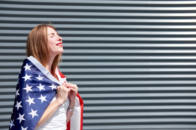 Usa stars and stripes flag. smiling beautiful ginger woman with red painted lips and closed eyes standing with usa flag and enjoying the sun. grey metal panel background.