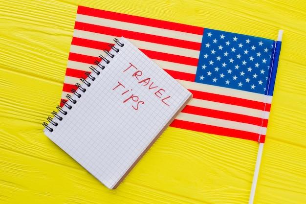 アメリカ旅行のヒントのコンセプト。黄色の木製テーブルの米国旗とメモ帳を閉じます。