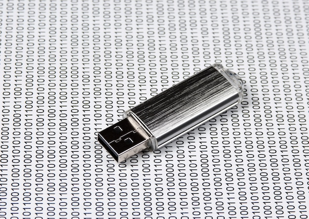 Usb flash drive on the background of a binary code