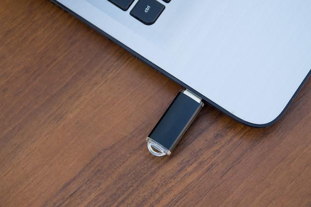 나무 책상에 있는 노트북 컴퓨터 측면에 부착된 usb 메모리 스틱 또는 플래시 드라이브