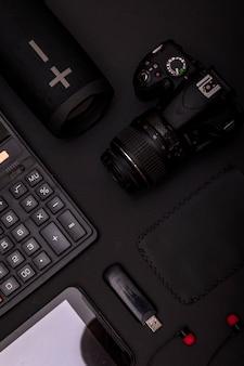 電卓、usbドライブ、イヤホン、デジタル一眼レフカメラ、ワイヤレススピーカー付きの黒いオフィスデスクの平面図です。