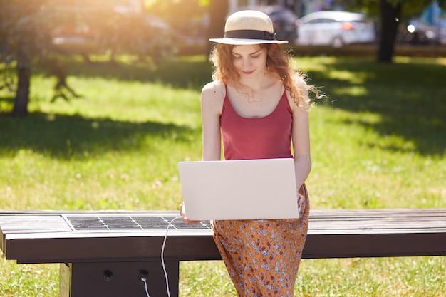 麦わら帽子に座って物思いにふける若い女性を集中し、白いラップトップをかざし、画面を注意深く見て、デバイスをusbで充電し、昼食時に屋外で働いていました。若者のコンセプトです。