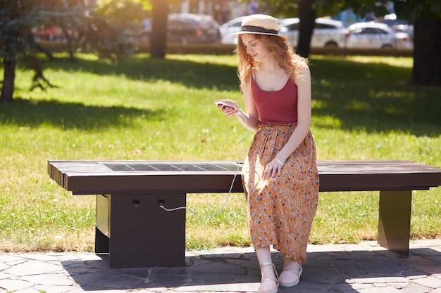 若い女の子の画像は、屋外のusbを介して携帯電話を充電し、町の公園の太陽電池パネルのベンチに座っている女性。公共充電、近代的な技術、代替電力、再生可能エネルギーの概念。