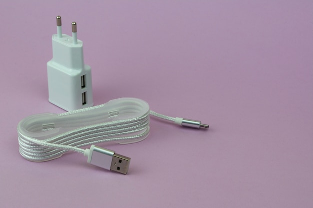 ピンクの背景にモバイルデバイス用のusb充電とケーブル。