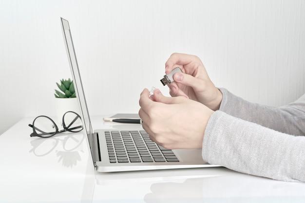 ノートパソコン、オフィスワークの概念の横にあるusbフラッシュを開く人