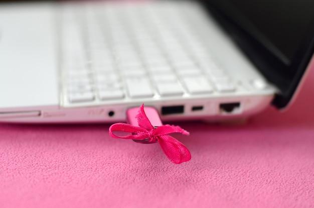 ピンクの弓と鮮やかなピンクのusbフラッシュドライブは白いラップトップに接続されています
