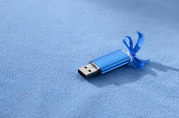 青い弓と鮮やかなブルーのusbフラッシュメモリカードは、柔らかく毛皮のようなライトブルーのフリース生地の毛布にあります。