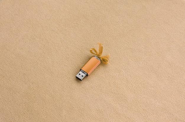 オレンジ色のusbフラッシュメモリカード(青いリボン付き)は、柔らかく毛皮のような淡いオレンジ色のフリース生地の毛布の上にあります。