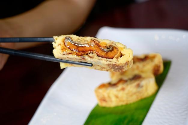 Используйте палочки для еды, чтобы обрабатывать японские яичные рулетики с жареным угрем (unagi) на белой тарелке