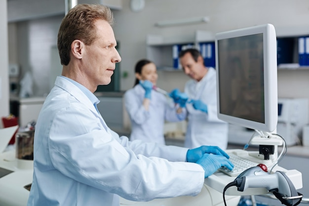 デバイスを使用します。血液分析をチェックしながらキーボードに指を置いてセミポジションに立っている非常に気配りのある男性