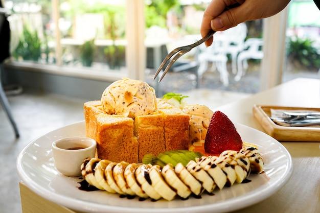 포크를 사용하여 혼합 과일, 슬라이스 바나나, 아이스크림과 함께 제공되는 허니 토스트 빵을 먹습니다.