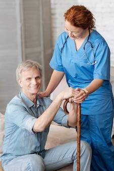 걷는 데 사용하십시오. 아름다운 사랑스러운 상냥한 간호사가 그에게 의료 서비스를 제공하고 그가 나아지는 것을 확인하면서 성숙한 신사의 느낌을 묻는다.