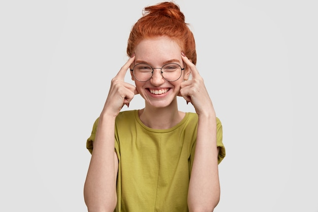 Используй свой мозг. счастливая рыжеволосая девушка держит оба указательных пальца на висках, пытается подумать, прежде чем действовать глупо, радостно улыбается, одетая в повседневную летнюю одежду, стоит у белой стены.