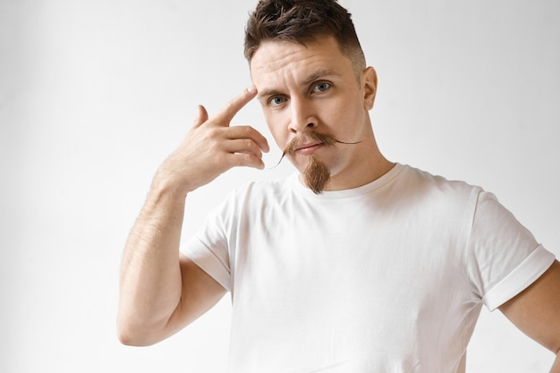 Use your brains. studio portrait of emotional handsome man with trimmed beard and handlebar mustache having displeased look, holding fore finger at his temple and rolling it, saying: are you crazy?