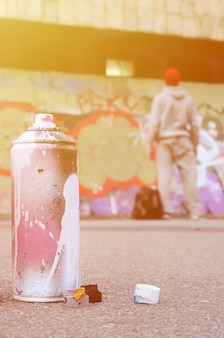 Used aerosol paint spray can with pink and white paint lie on the asphalt