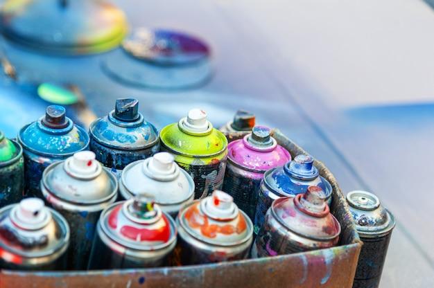 판지에 있는 깡통에 있는 사용된 에어로졸 스프레이 페인트.
