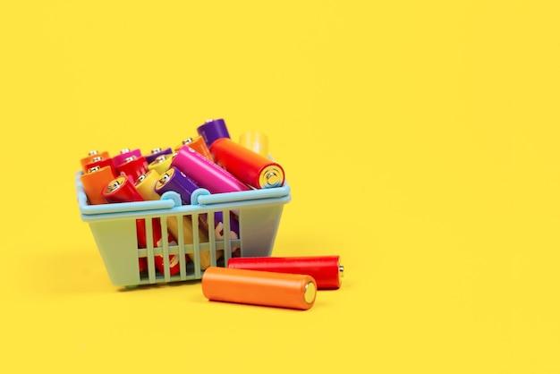 Использованные батареи в корзине супермаркета на желтом