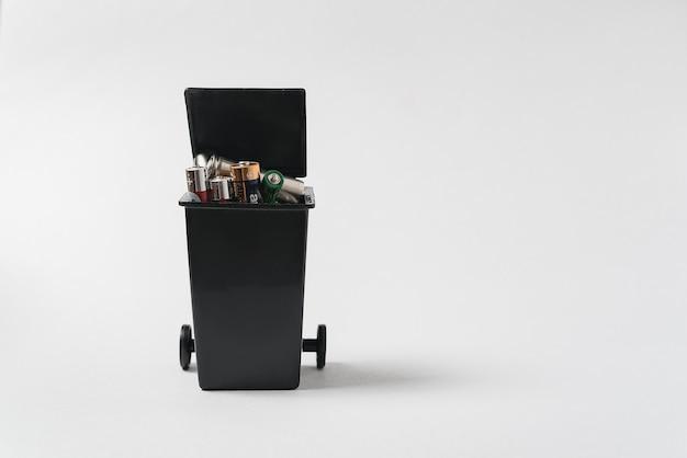 Использованные батареи в контейнере для мусора на белом фоне. загрязнение окружающей среды токсичными бытовыми отходами.