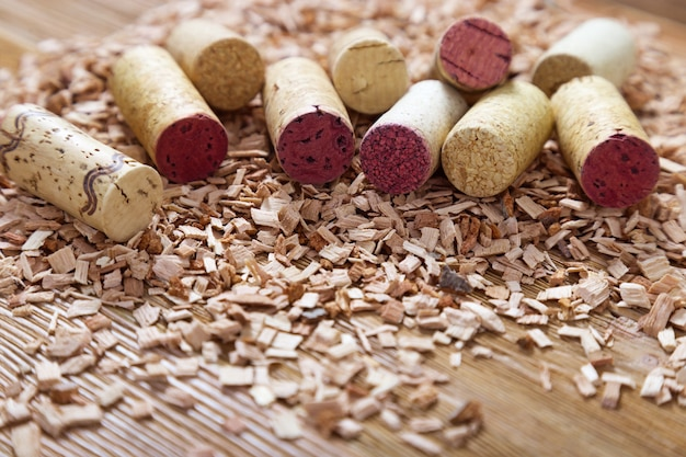 Used corks from wine spread out on wood sawdust.  natural wood materials with wine stoppers. selective focus. copy space.