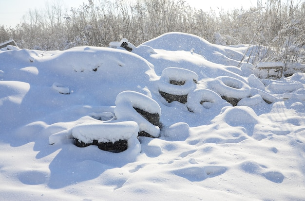 Used and discarded car tires lie on the side of the road, covered with a thick layer of snow