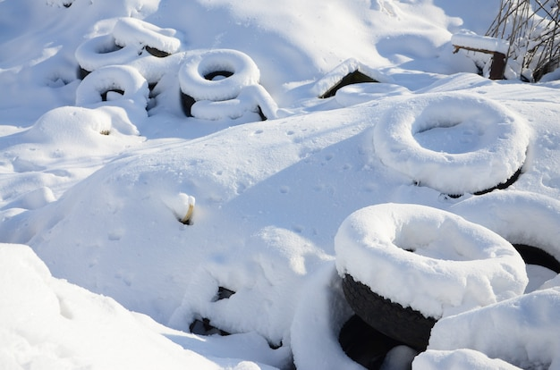 Used and discarded car tires lie on the side of the road, covered