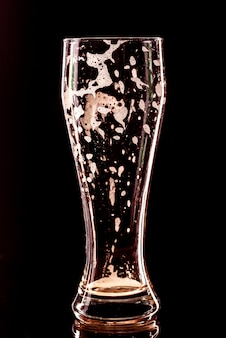 Used empty beer glass with drops on black. beer bubbles closeup