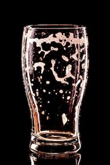 空のビールグラスに黒の滴を使用しました。ビールの泡のクローズアップ