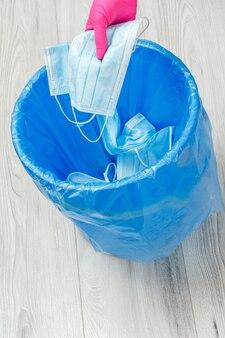 使用済みの医療用保護マスク。パンデミック時の個人保護手段を利用するためのゴミ箱。ニトリル手袋と青いゴミ袋を手に入れます。環境の汚染。上面図。