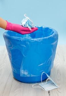 使用済みの医療用保護マスク。パンデミック時の個人保護手段を利用するためのゴミ箱。ニトリル手袋と青いゴミ袋を手に入れます。環境の汚染。