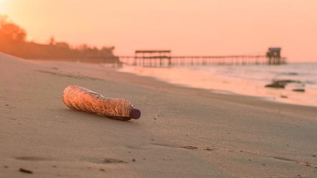 Бутылки использованного масла на пляже на закате