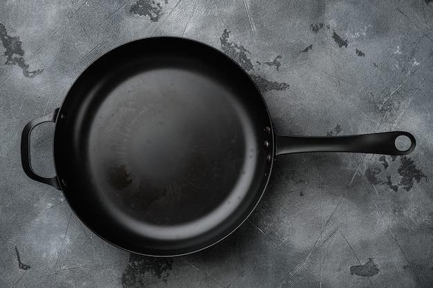 Использованная старая пустая сковорода с копией пространства для текста или еды с копией пространства для текста или еды, плоская планировка, вид сверху, на фоне серого каменного стола