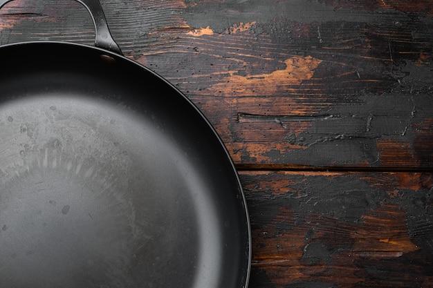 Использованная старая пустая сковорода с копией пространства для текста или еды с копией пространства для текста или еды, плоская планировка, вид сверху, на фоне старого темного деревянного стола
