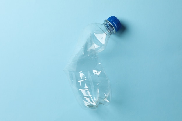 Used plastic bottle on blue, space for text