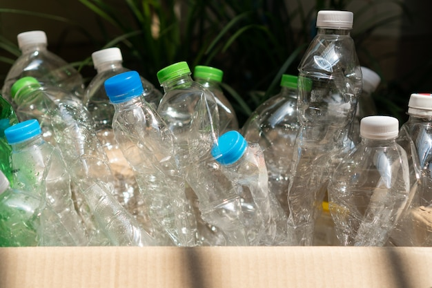Used plastic bottle in the box, recycling plastic utilisation concept. ecological problem, environmental pollution. close up