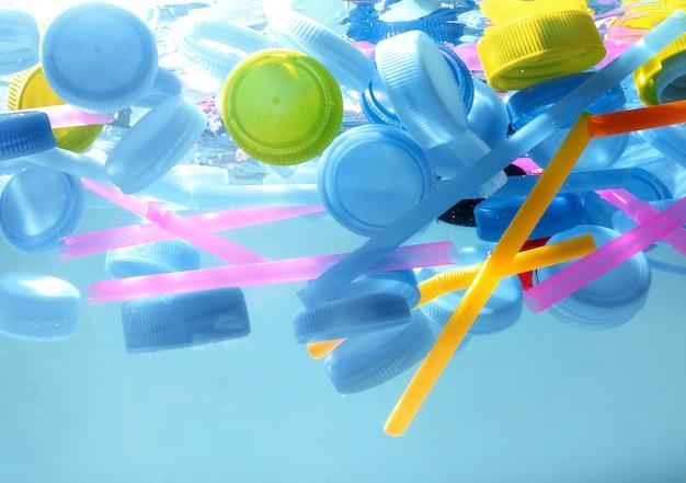 더러운 물에 사용 된 플라스틱 병 마개. 환경주의와 플라스틱 인식.