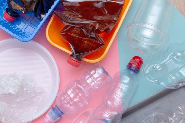 Использованные пластиковые мятые пустые бутылки пакеты контейнер для посуды красочный фон крупным планом