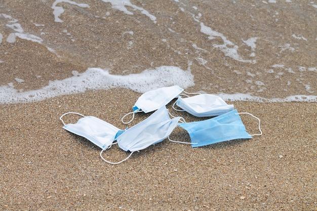 海のプラスチック汚染の概念に廃棄された使用済み保護フェイスマスク