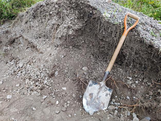 Б / у лопата рядом с кучей гравия