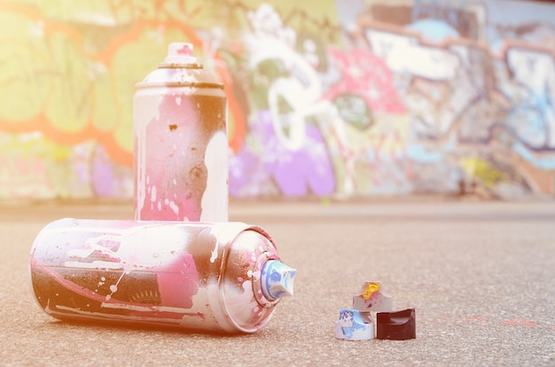 Использованные баллончики с розовой и белой краской и колпачки для распыления краски