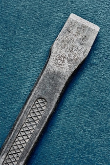 Used stone chisel on blue background, macro, top view