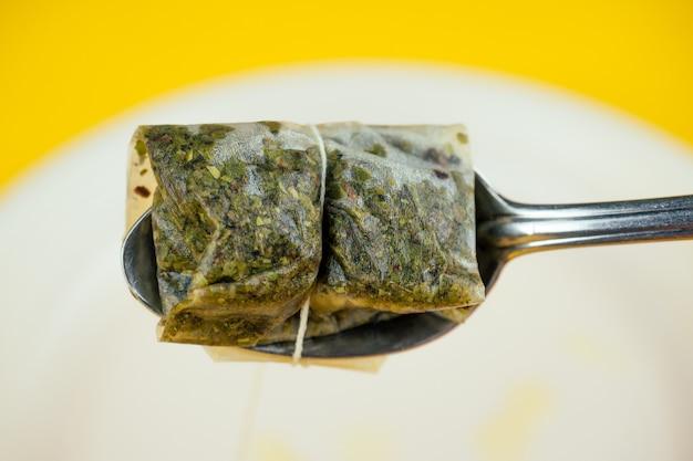 노란색 배경에 금속 스푼이 있는 플라스틱 접시에 사용된 티백